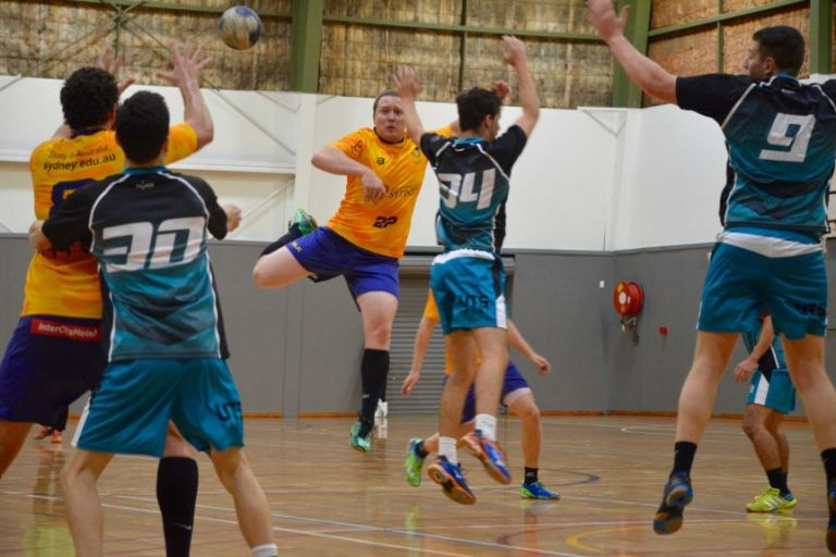 Handball player in mid-air passes to team mates as defenders try to disrupt the pass
