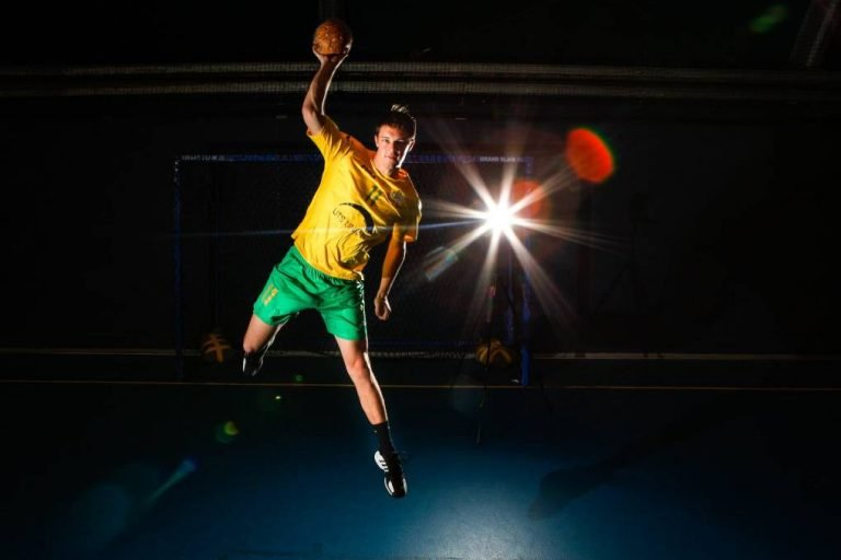 Luke Behrendorff in mid-air throwing a handball