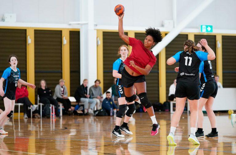 Sophoie Marie Angelique in midair throwing towards goal
